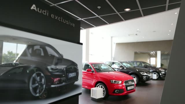 A female customer inspects a red Audi Q3 automobile on display inside an Audi AG showroom in Moscow Russia on Saturday Aug 2 Audi A3 Sportback...