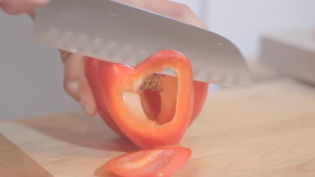 Female cuts red pepper on wood plate