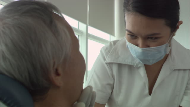 CU, Female dentist treating male patient, Singapore