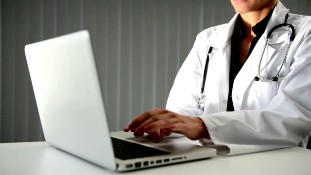 Female doctor hand typing on laptop