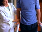 Female doctor helping middle-aged male patient with leg brace walk slowly in physical therapy