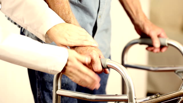 Female doctor helps senior man patient use walker. Holding hands.