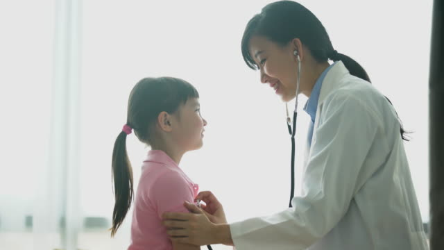 MS female doctor listing to the heart of a young girl