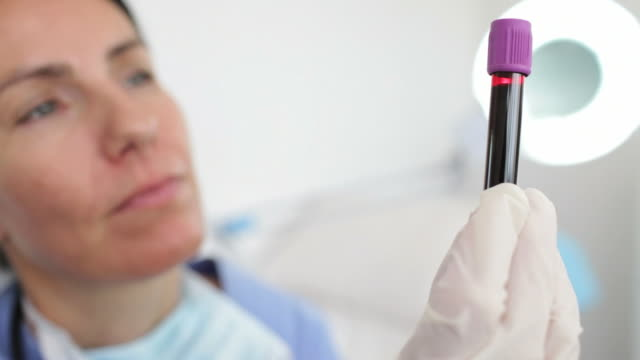 Female doctor looking at blood sample