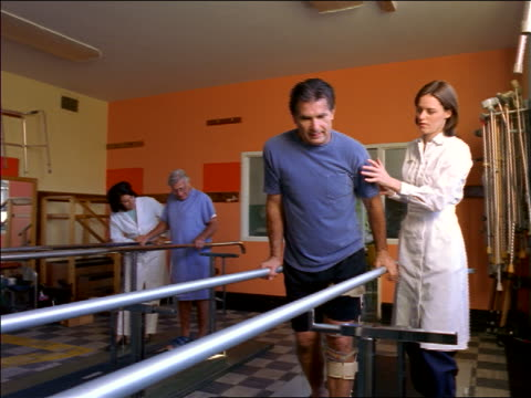 Female doctor + nurse helping 2 male patients (1 senior) walk slowly in rehab / physical therapy
