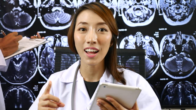 Female doctor on video call from her Office with X-ray image of the brain computed tomography on Background