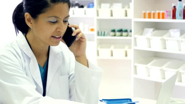 Female doctor or pharmacist uses smart phone and laptop at work