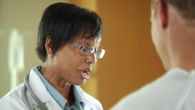 CU TU Female doctor talking to patient in hospital, Seattle, Washington, USA