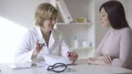 Weiblich Arzt mit Patienten reden