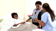 Female doctor with African mother and daughter in hospital