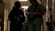 Female doctors and nurses in scrubs walking in corridor smiling