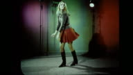 HD Female dressed in sweater skirt boots DROP FRAMES STOP MOTION Dancing in lighted studio w/ magenta green red lighting on wall BG 1960s free form...