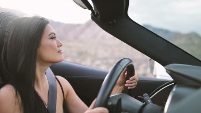 Female driving convertible car on roadtrip