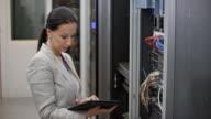 LD vrouwelijke ingenieur controle van een rek in de serverruimte