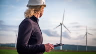 Female engineer in front of wind turbines - Women in STEM