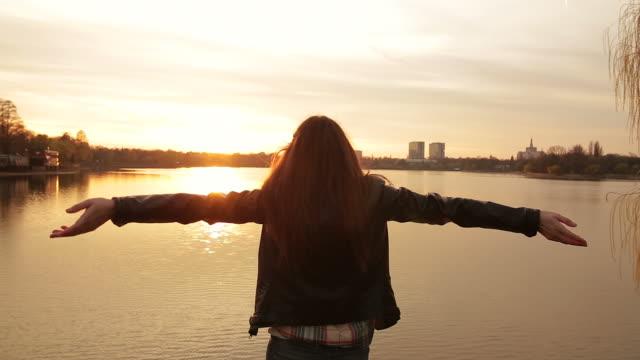 Female enjoying sunset on the edge of the lake.