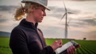 Female environmental engineer Women in front of wind turbines - Women in STEM