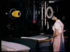 Female factory worker moving foamex foam sheet on machine table for pressing rod MS Female workers putting foamex pillows into pillow cases in...