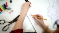 Female fashion designer hands holding drawing pad and pen making sketch of new dress.
