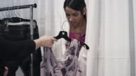 MS Female fashion model backstage at fashion show peaking out from behind changing curtain wardrobe stylist handing model dress