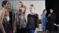 MS Female fashion models backstage at fashion show taking photo with smart phone