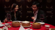 Female feeding male with dumplings in Chinese restaurant
