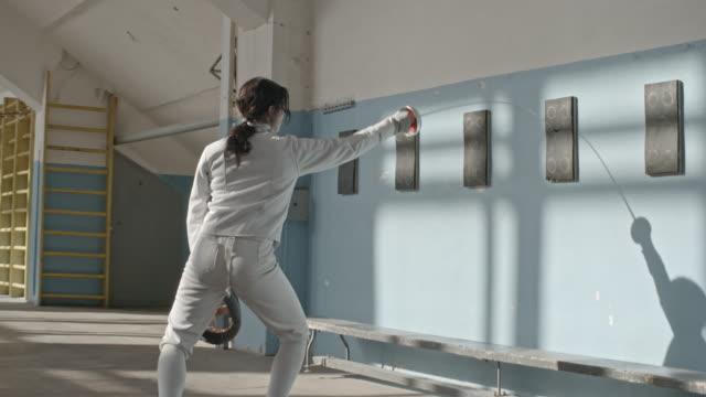 Female fencer perfecting skills