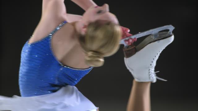 SLO MO Di weibliche skater performing catchfoot layback spin Vielfalt