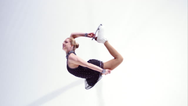 SLO MO vrouwelijke kunstschaatsster uitvoeren van variatie van cirkel spin