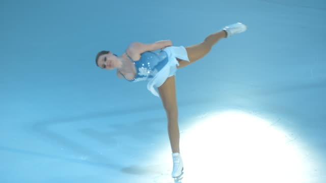 SLO MO Female figure skater spinning in parallel spin variation