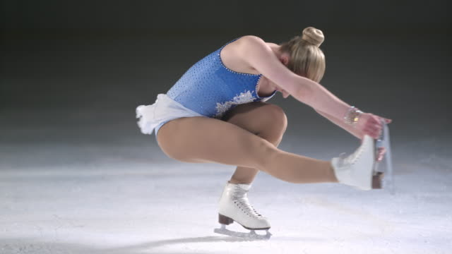 SLO MO LD Female figure skater spinning in sit spin position