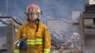 Female firefighter in front of smoldering ruins of a totally destroyed house