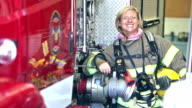 Female firefighter standing beside fire engines