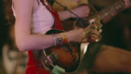 Female folk musicians play mandolin and acoustic guitar together on stage