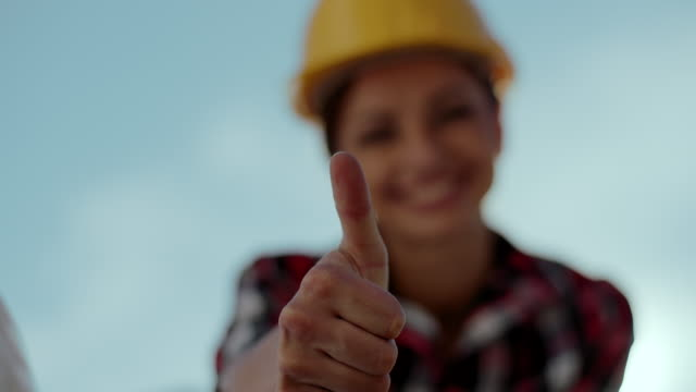 Female foreman showing thumbs up