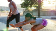 MS Female friends in discussion while stretching before early morning run