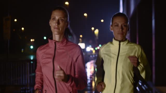 SLO MO femmina amici fare jogging nella città di notte