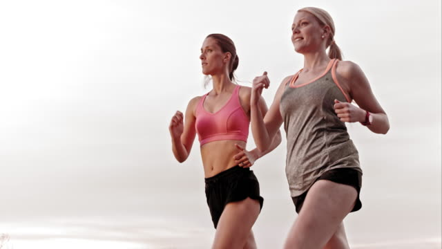 SLO MO TS Female friends jogging together and smiling