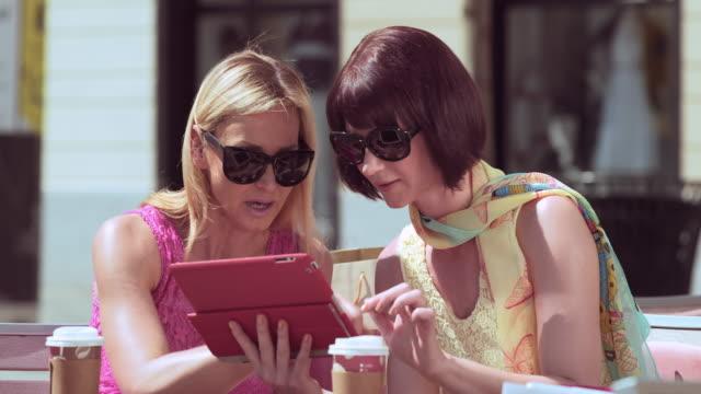 Freundinnen im Freien sitzen und sich unterhalten und Sie an einem tablet arbeitet