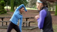 MS Female friends stretching near trail in park before morning run