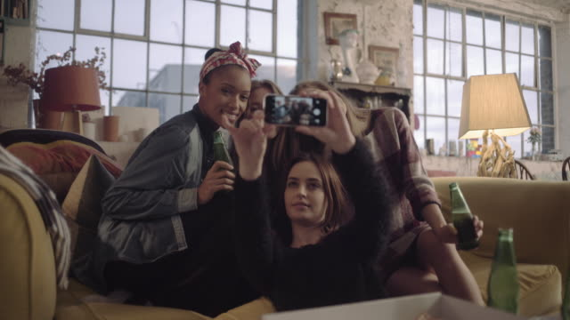 Female friends taking hanging out and take selfie at home