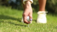 Female golfer hand pushing tee into grass