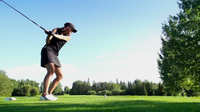 Female golfer tees off.