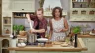 DS Female guest on the cooking show observing the male host cooking and talking to him and the viewers