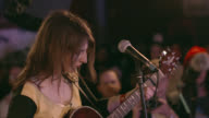 Female guitarist rocks out with acoustic guitar at crowded rock show