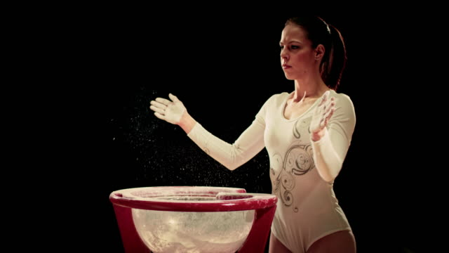 SLO MO Female gymnast clapping her chalky hands