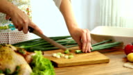 Female hand cutting green onions on board with knife