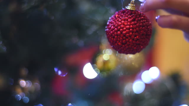 female hand hangs a Christmas ball on the Christmas tree