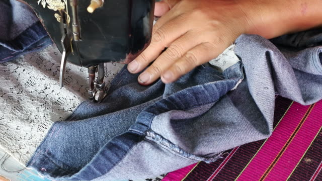 Female hand repair of denim with old machine.