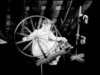Female hand spinning yarn on spinning wheel MS Yarn on spinning wheel VS loading dark thread onto bobbin Americana artisan